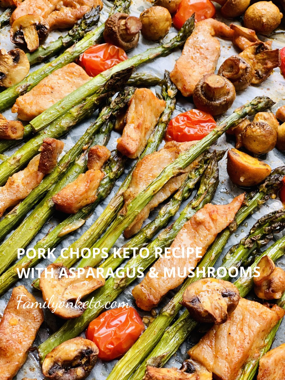 Picture of pork chops in a baking tray baked with asparagus, mushrooms and cherry tomatoes