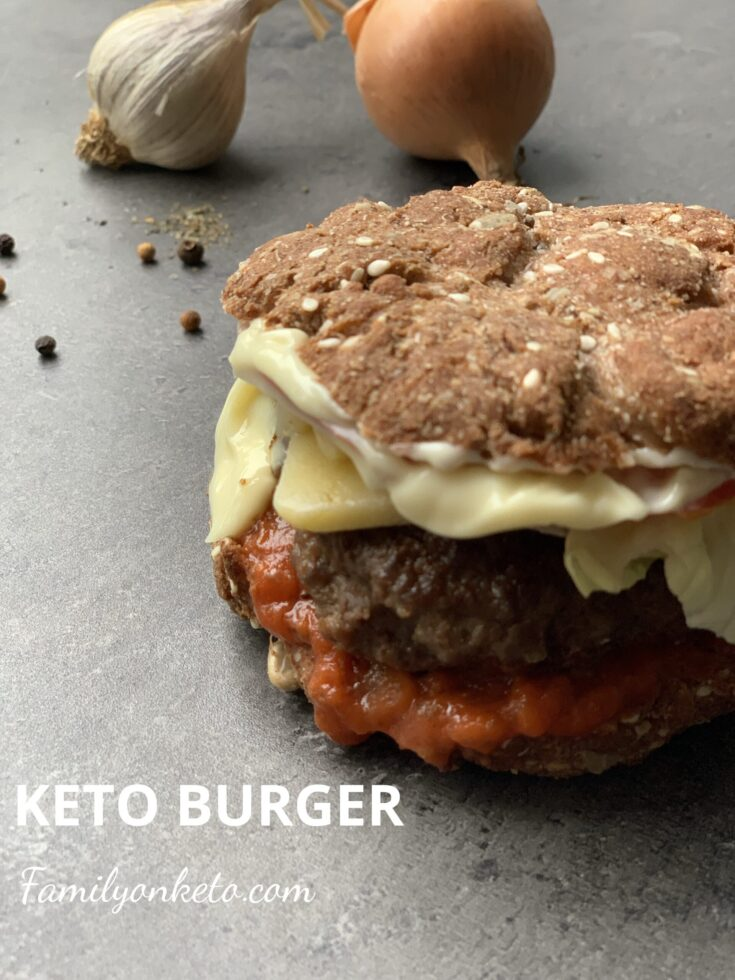 Picture of a keto burger in a keto bun with mayonnaise and keto tomato sauce