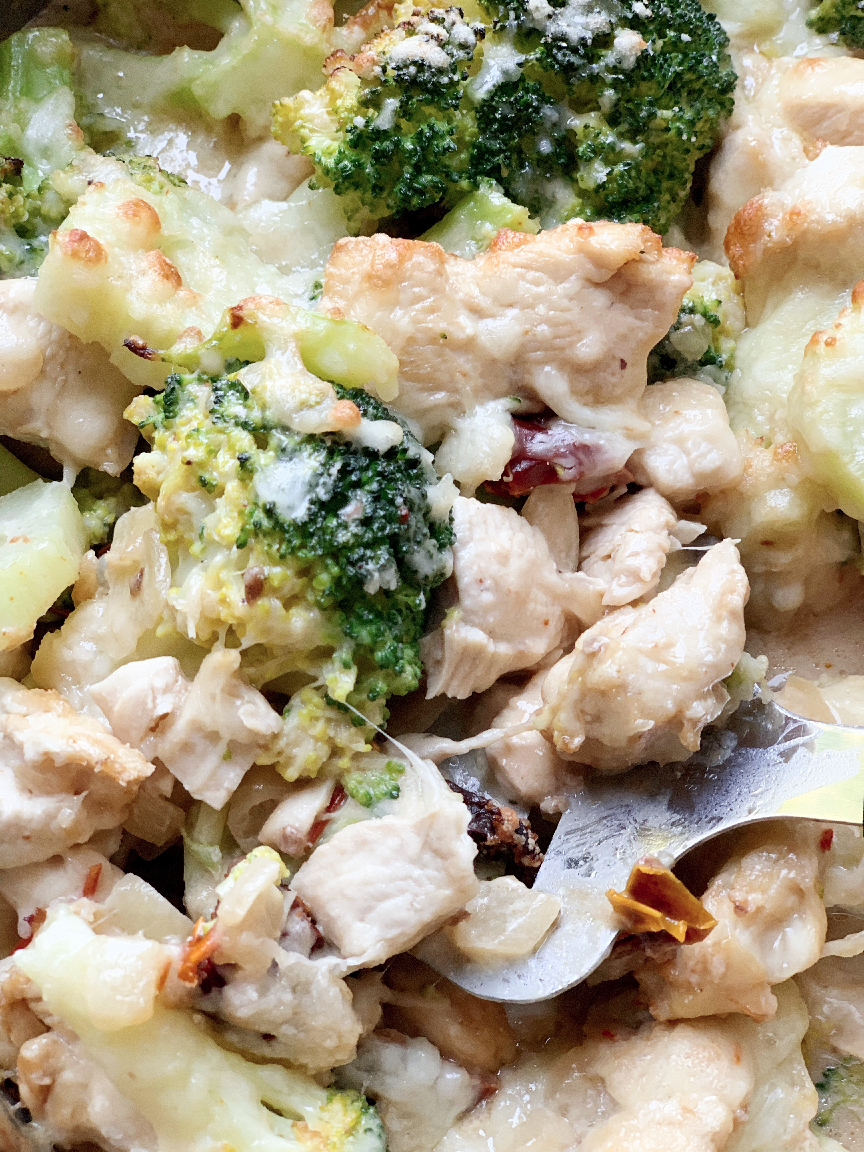 Picture of keto broccoli and chicken casserole with sun dried tomato sauce and mascarpone cheese in skillet