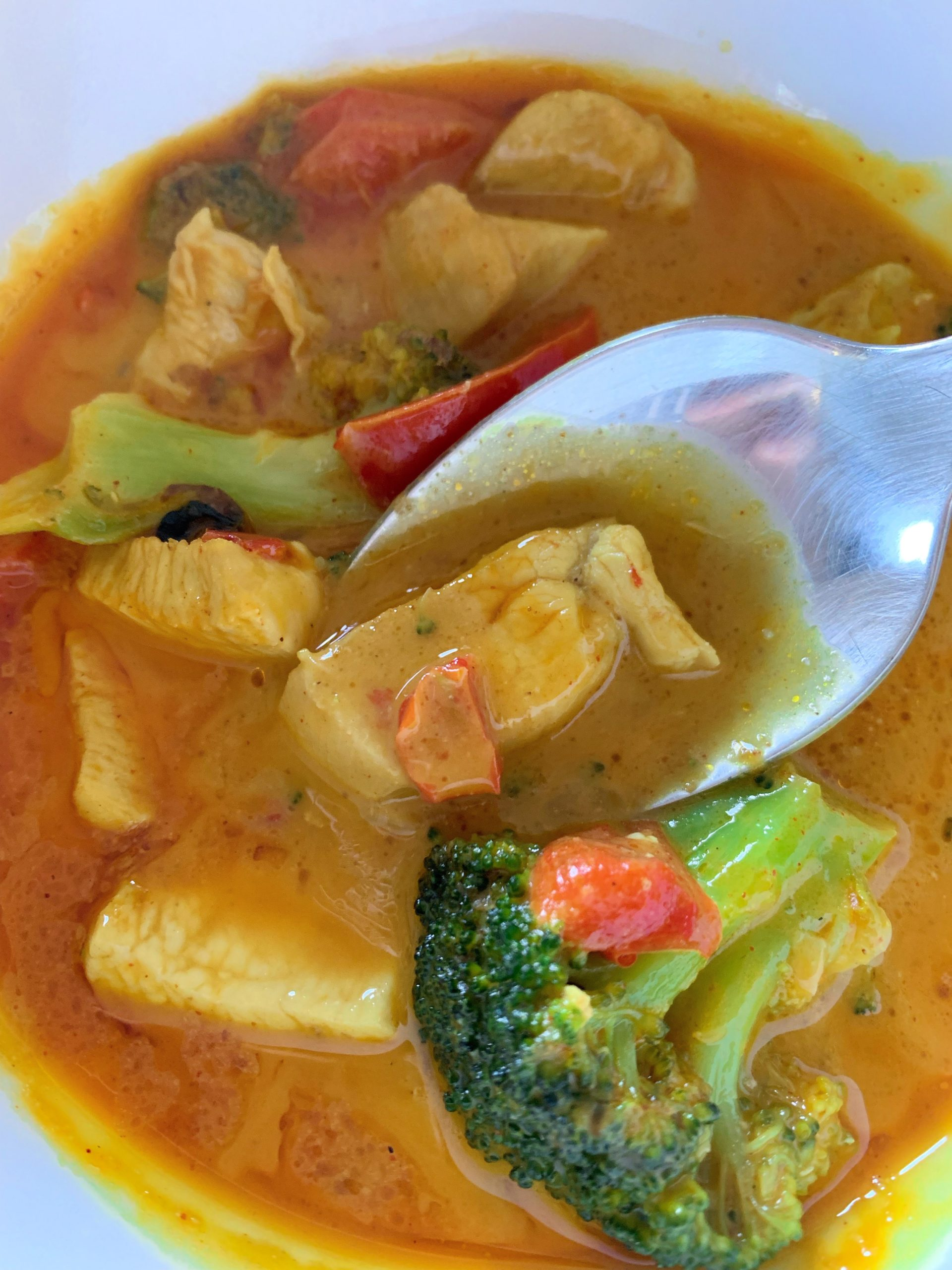 Picture of low carb chicken curry soup in a bowl on a spoon