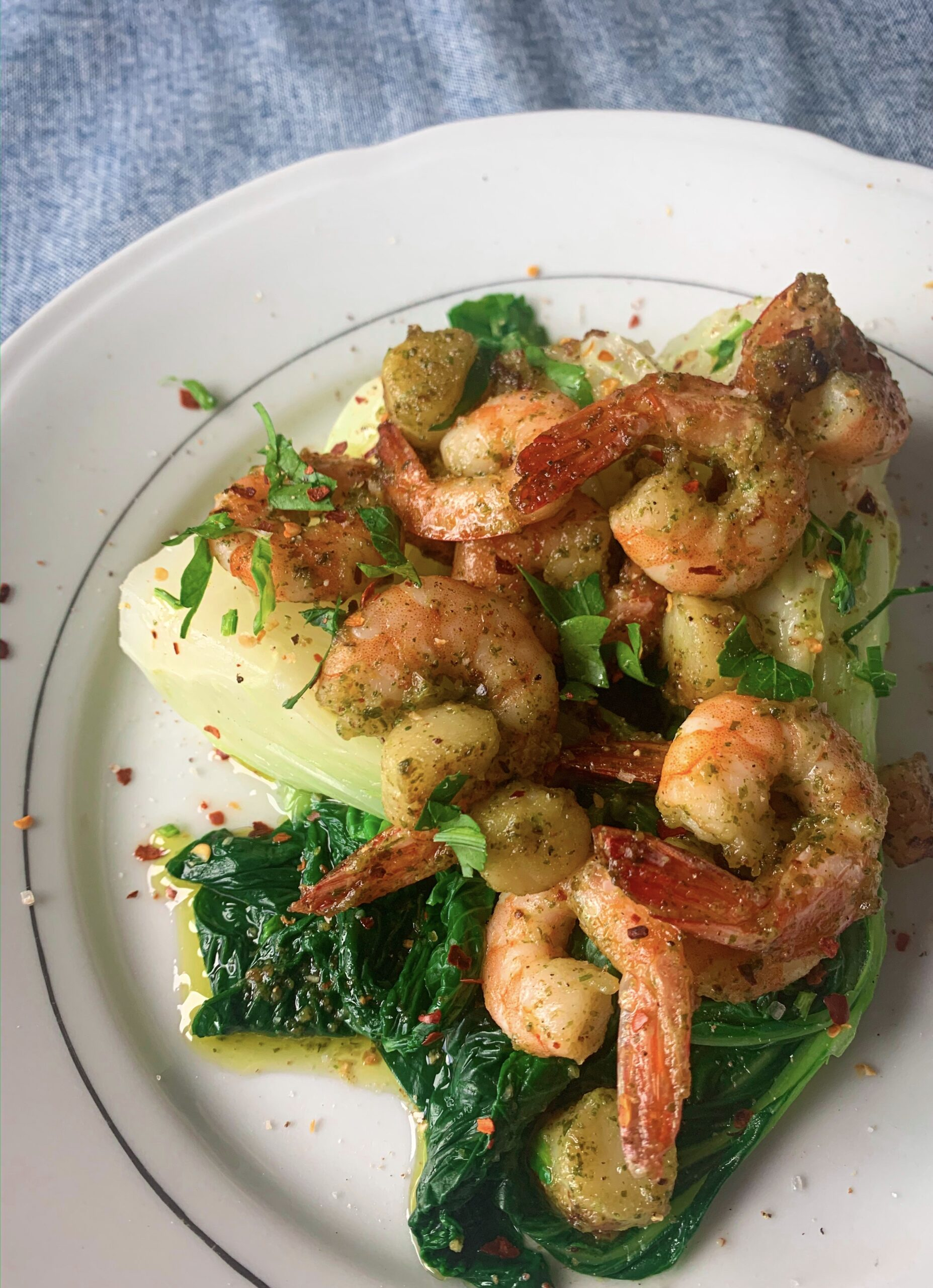 Picture of a plate full of bok choy with scallops and prawns seasoned with garlic and chilli