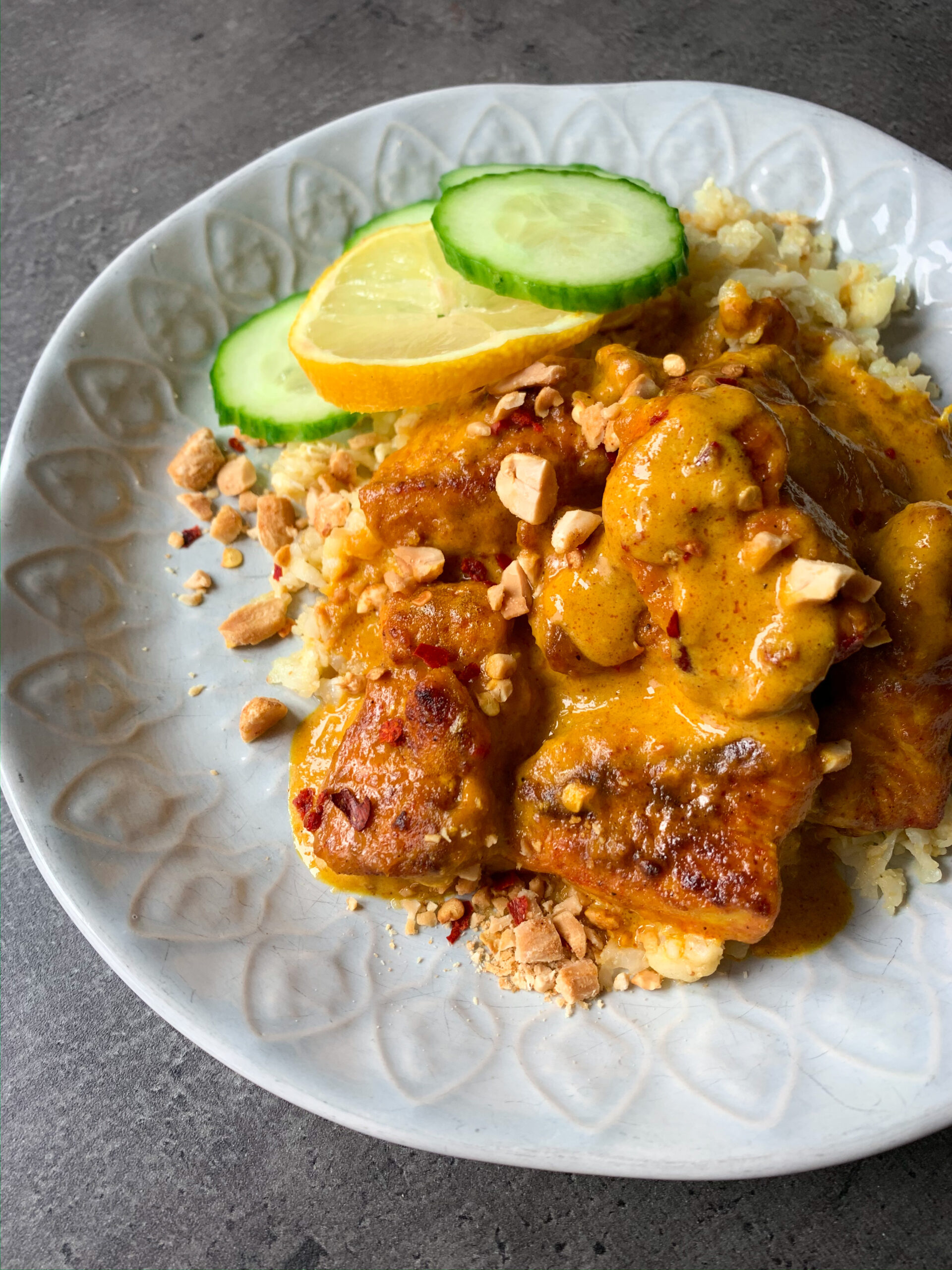 Picture of chicken with peanut sauce recipe in a plate with riced cauliflower