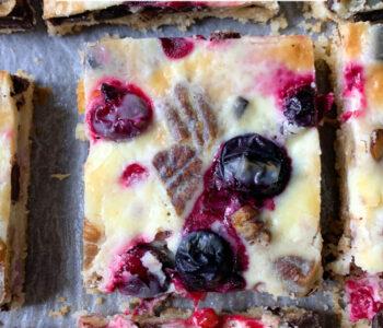 Photo of keto magic cookie bars with berries, pecans and dark chocolate and condensed keto milk cream