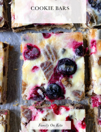 Photo of keto magic cookie bars with berries, pecans and dark chocolate and condensed keto milk cream
