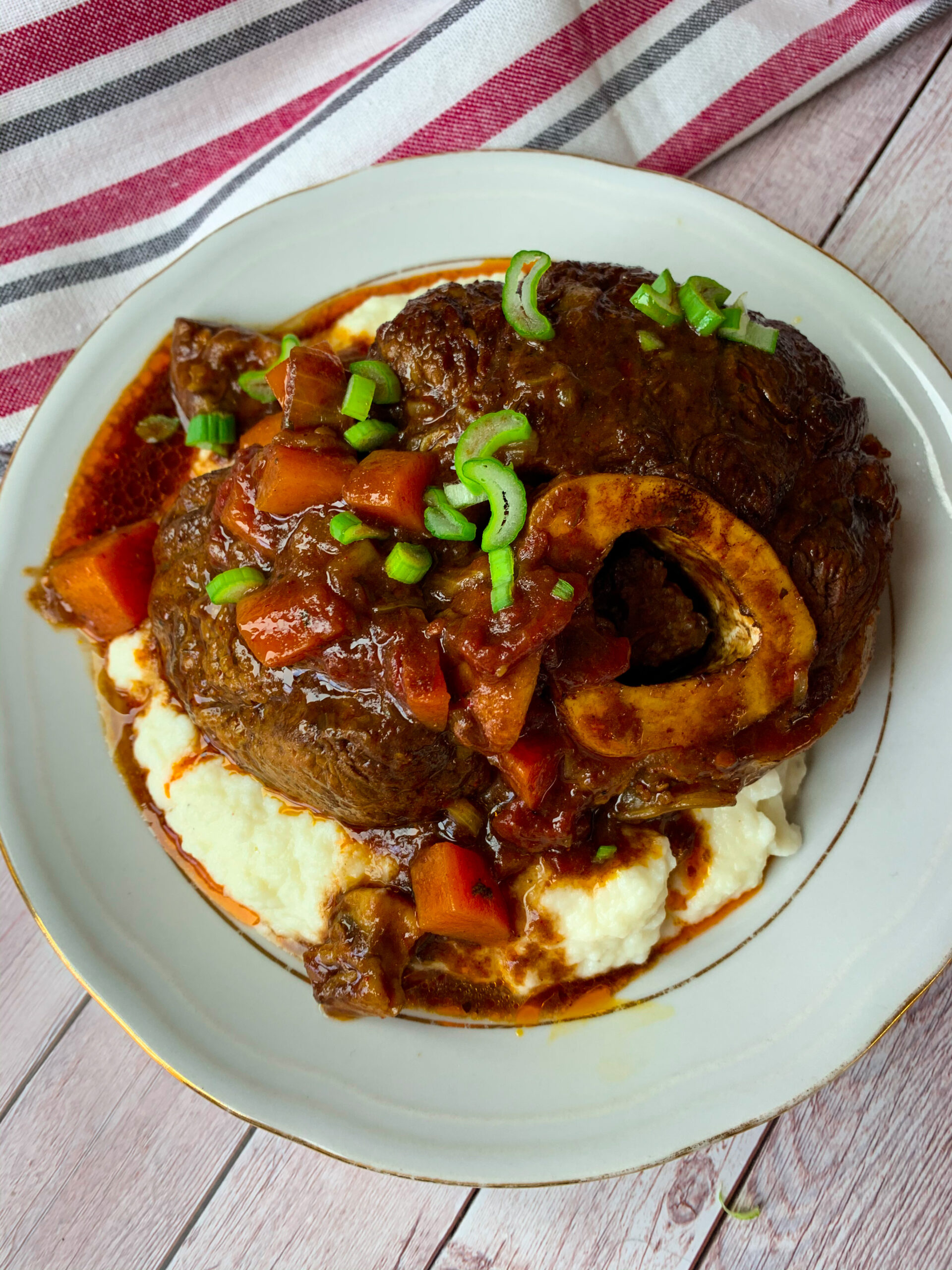 Beef ossobuco or keto osso buco with vegetable stew on a plate with cauliflower mash