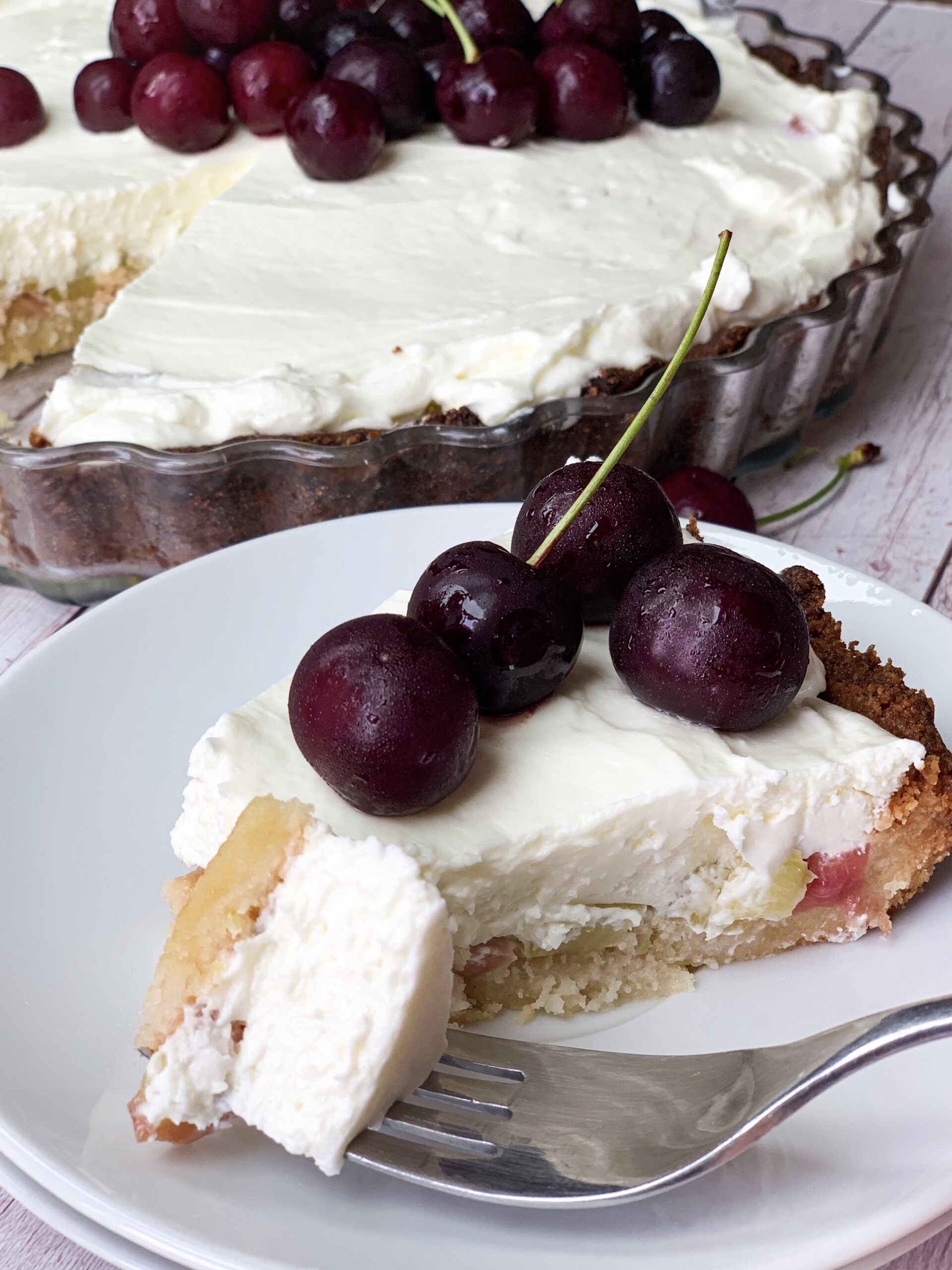 Piece of low carb rhubarb cheesecake with low carb pie crust and cherries on top