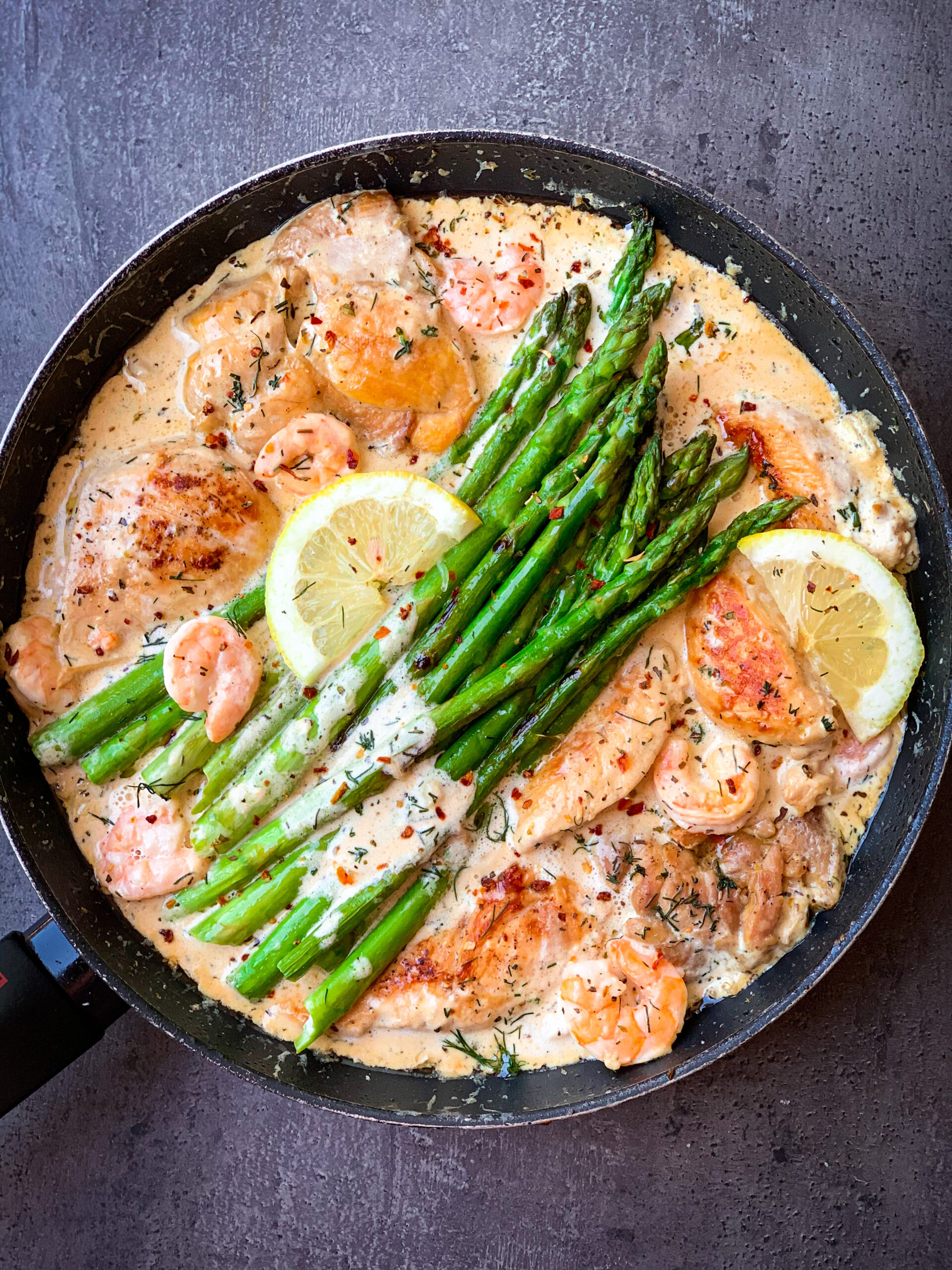 Picture of chicken with lemon butter sauce in one skillet with asparagus