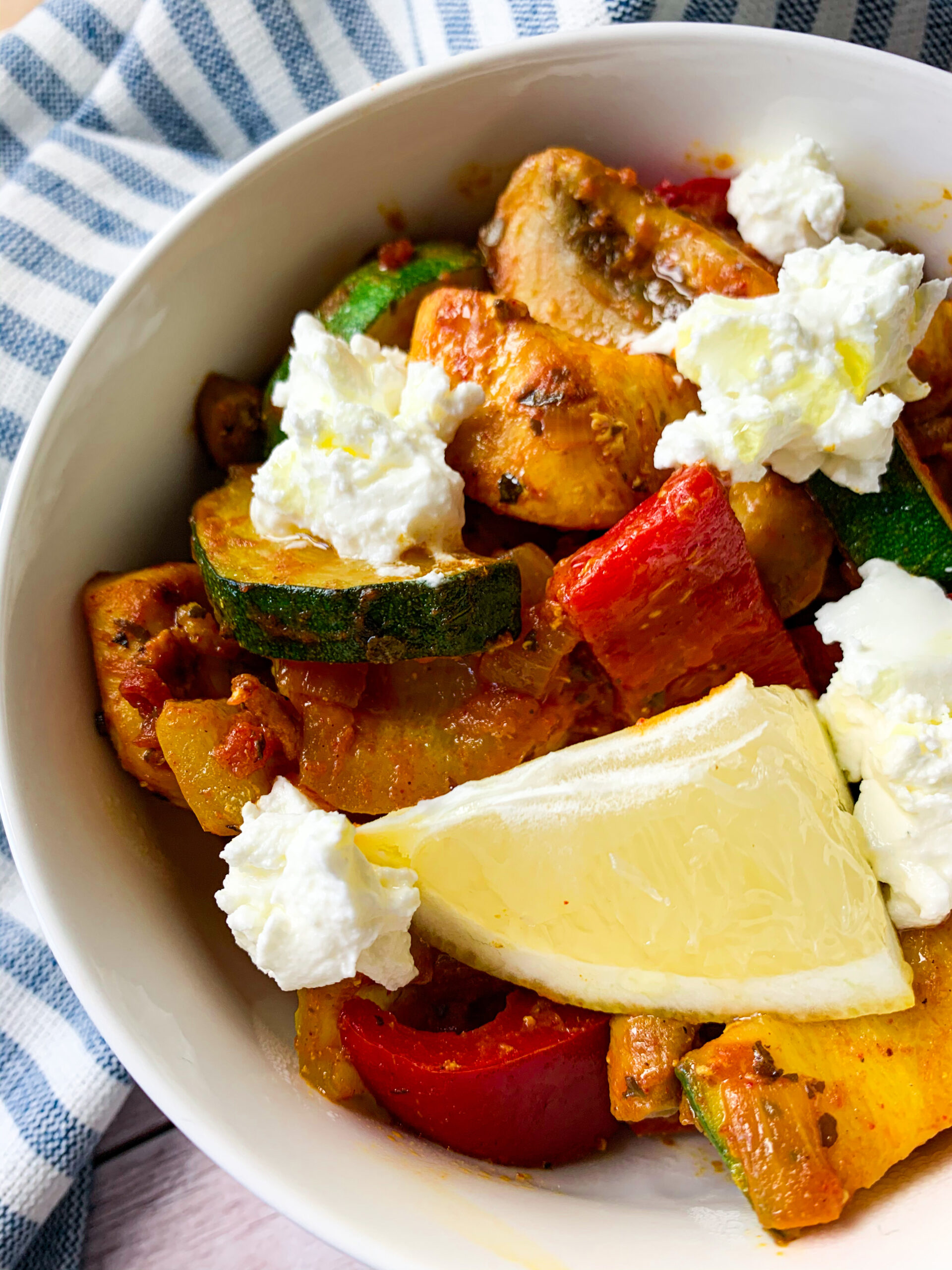 Picture of a bowl of chicken with vegetables and feta cheese on top
