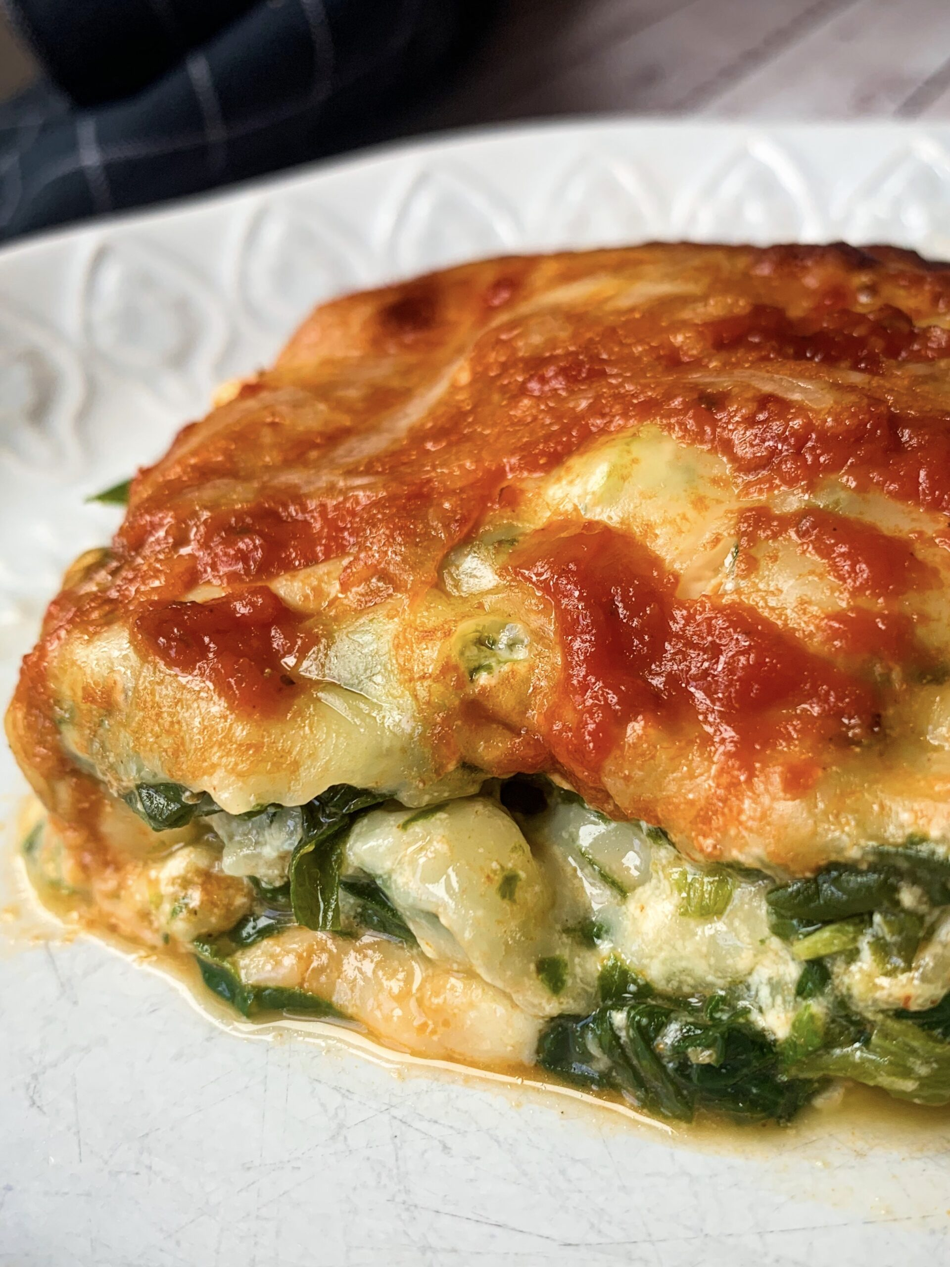 Picture of a slice of easy keto vegetarian lasagna with cheese and spinach