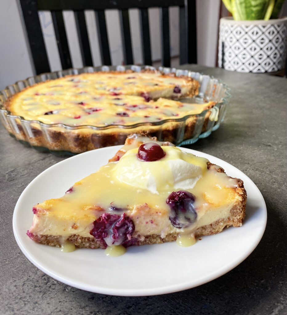 Picture of a sweet keto pie with cherries and silky vanilla cheesecake cream