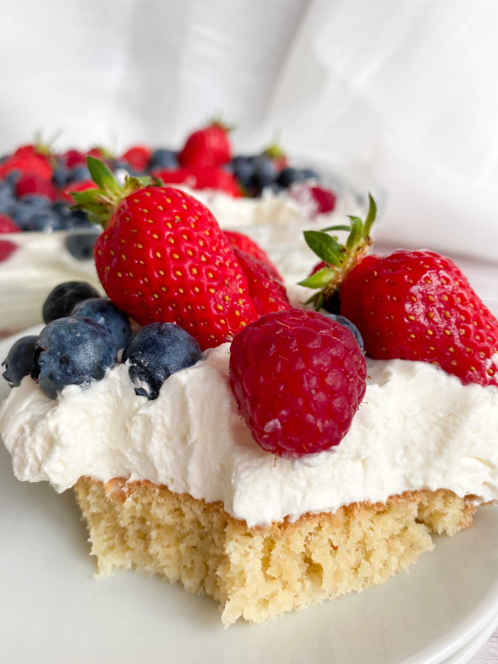 Photo of keto cake with berries and whipped cream