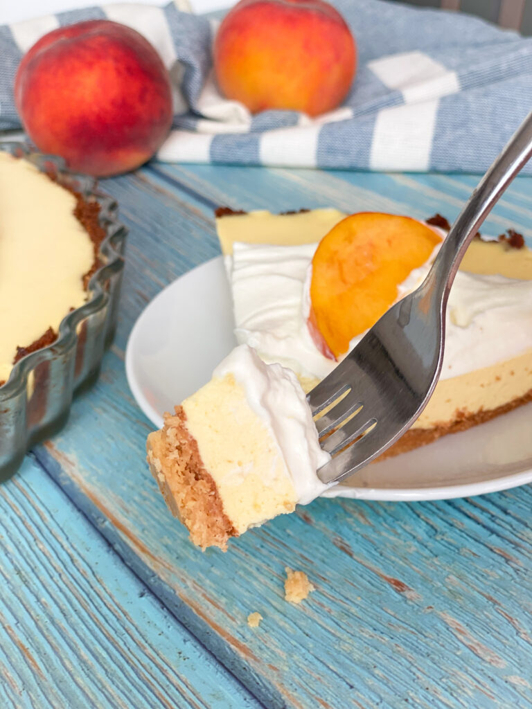 Picture of creamy keto peach pie piece on a fork and a slice of keto peach pie in the back