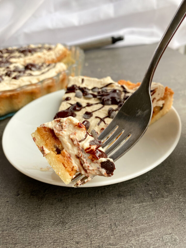 Picture of a piece of low carb peanut butter cookie dough pie with cream topping on a fork